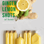 One whole and one half lemon with a ginger root and 7 small glass vials filled with ginger lemon shots laying on a flat surface