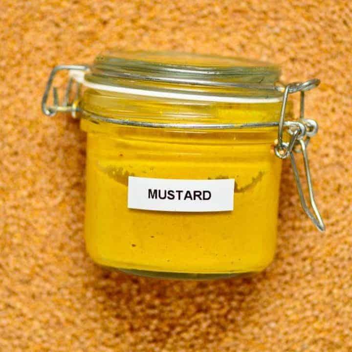 Mustard jar on top of mustard seeds