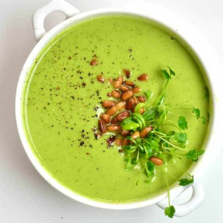 Pea soup topped with pepper and pine nuts