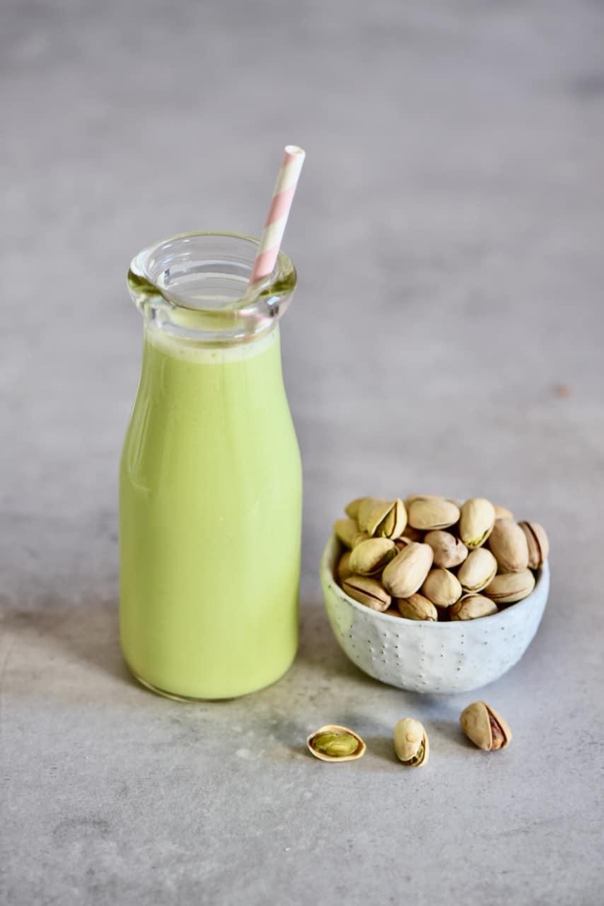 A mini bottle of pistachio milk and a bowl of pistachios