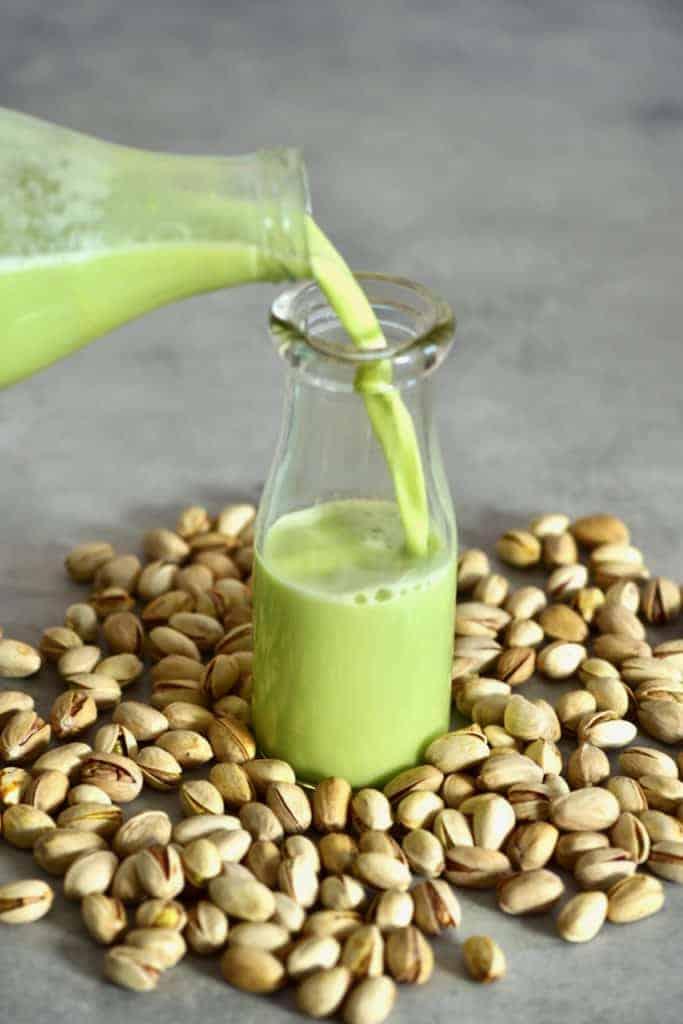 Pouring pistachio milk in a little bottle