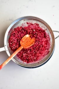 Mashed Pomegranate seeds in a sieve