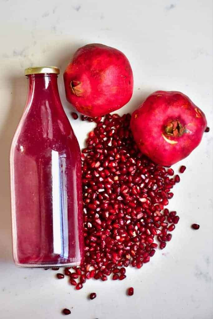 Pomegranate fruit seeds and juice in a bottle