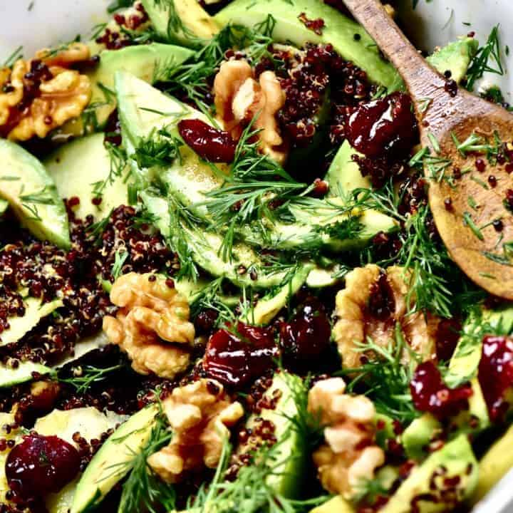 A close up of quinoa avocado apple and walnut salad with a wooden spoon