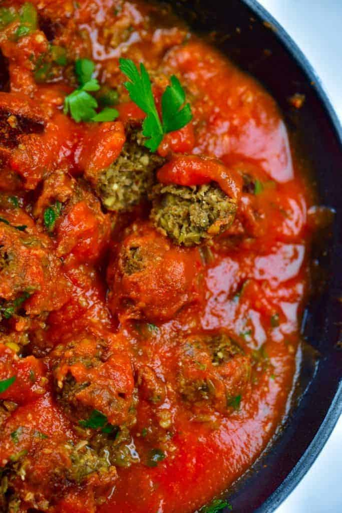 Showing lentil meatball in pan with tomato sauce
