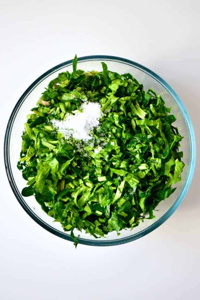 Chopped spinach and salt for Spinach Fatayer