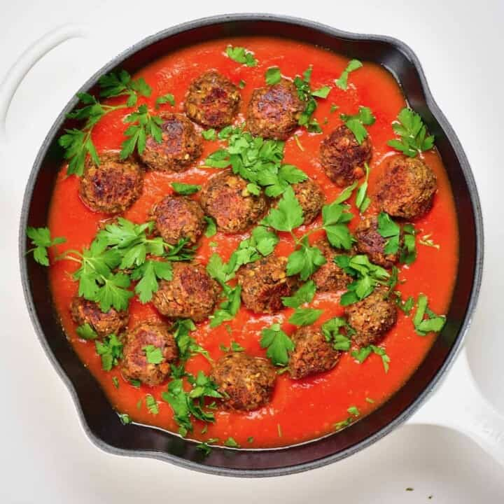 A large pan with mushroom and lentil vegan meatballs and tomato sauce topped with parsley