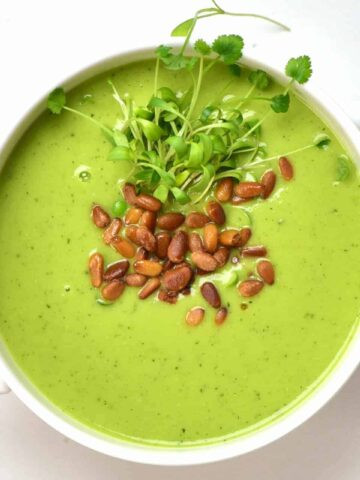 A bowl of pea soup with toasted pine nuts and micro greens on top