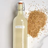 Flax Milk in a glass bottle and some flaxseeds next to it on a flat surface