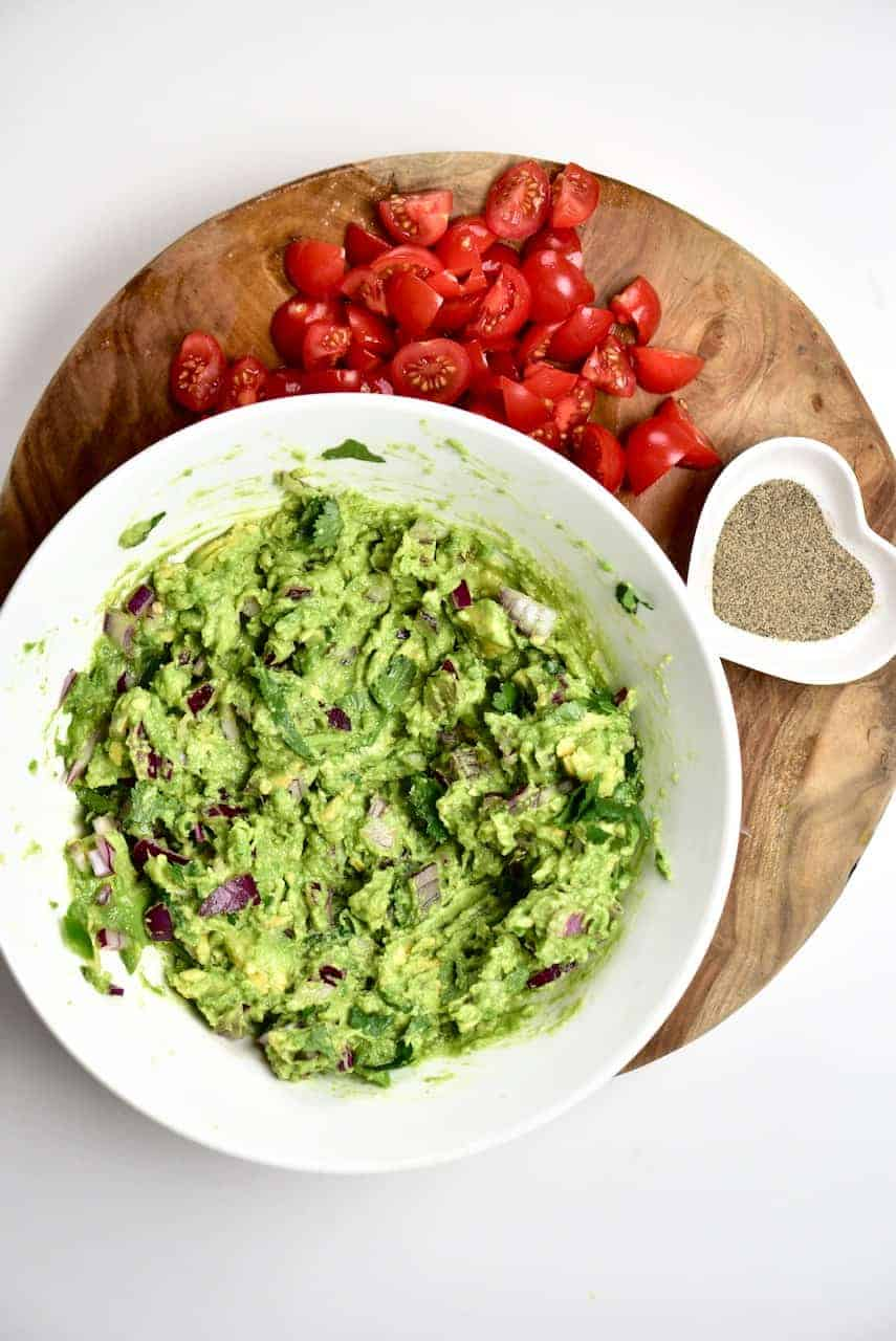 A bowl of guacamole and tomatoes