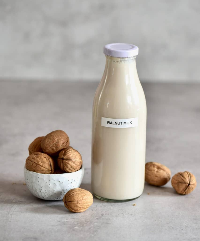Walnut milk in a bottle and walnuts