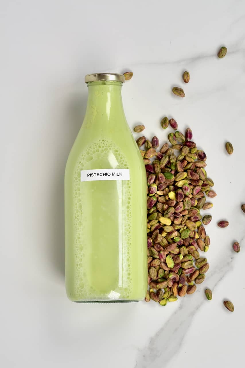 Pistachio milk in a bottle and pistachios on the side