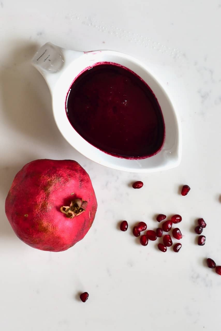Sugar-free Pomegranate Molasses in a bowl and pomegranate fruit