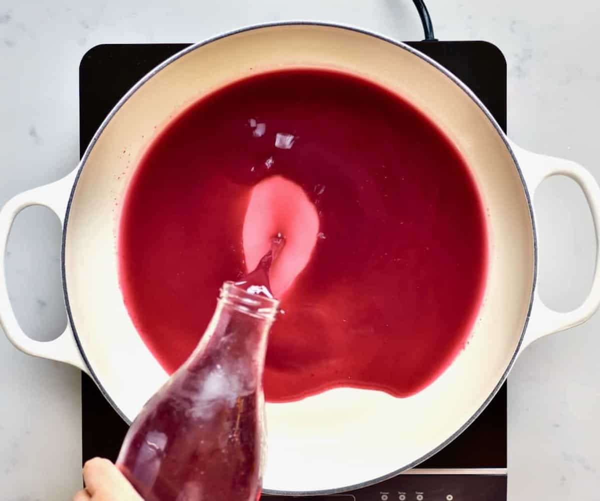 Pouring pomegranate juice in a pot