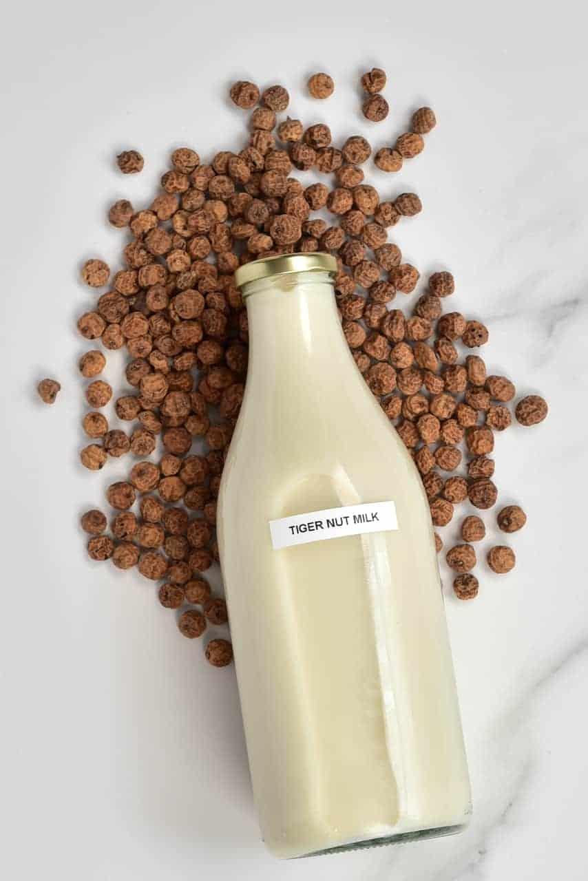 Tigernut Milk in a bottle and Tigernut tubers around it