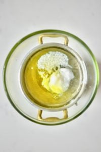 Mixing coconut oil olive oil beeswax and almond oil