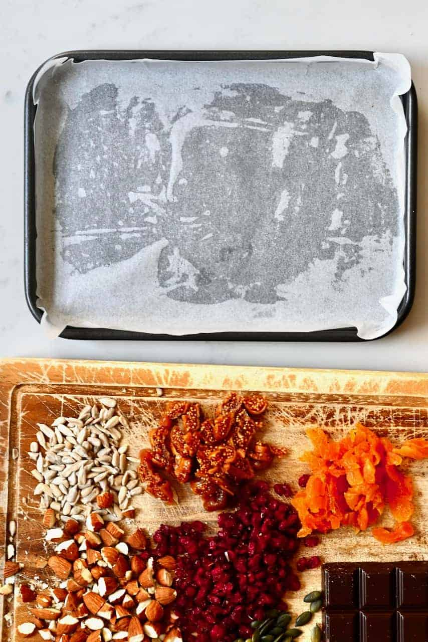 Baking sheet lined tray and chopped nuts and fruit