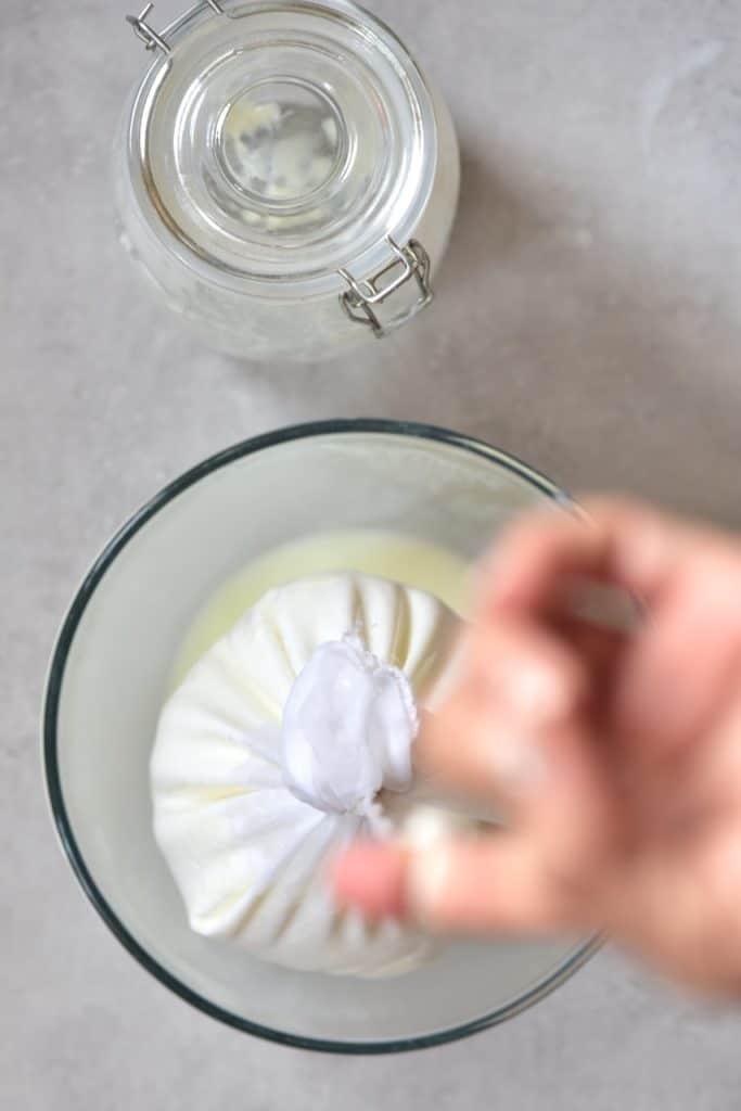 straining yogurt over a bowl, through a nut milk bag