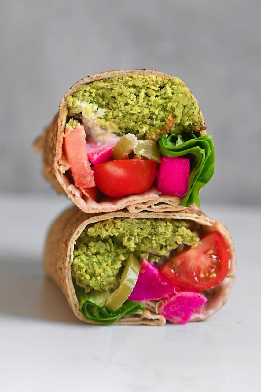 falafel sandwich cut in half showing all the fillings