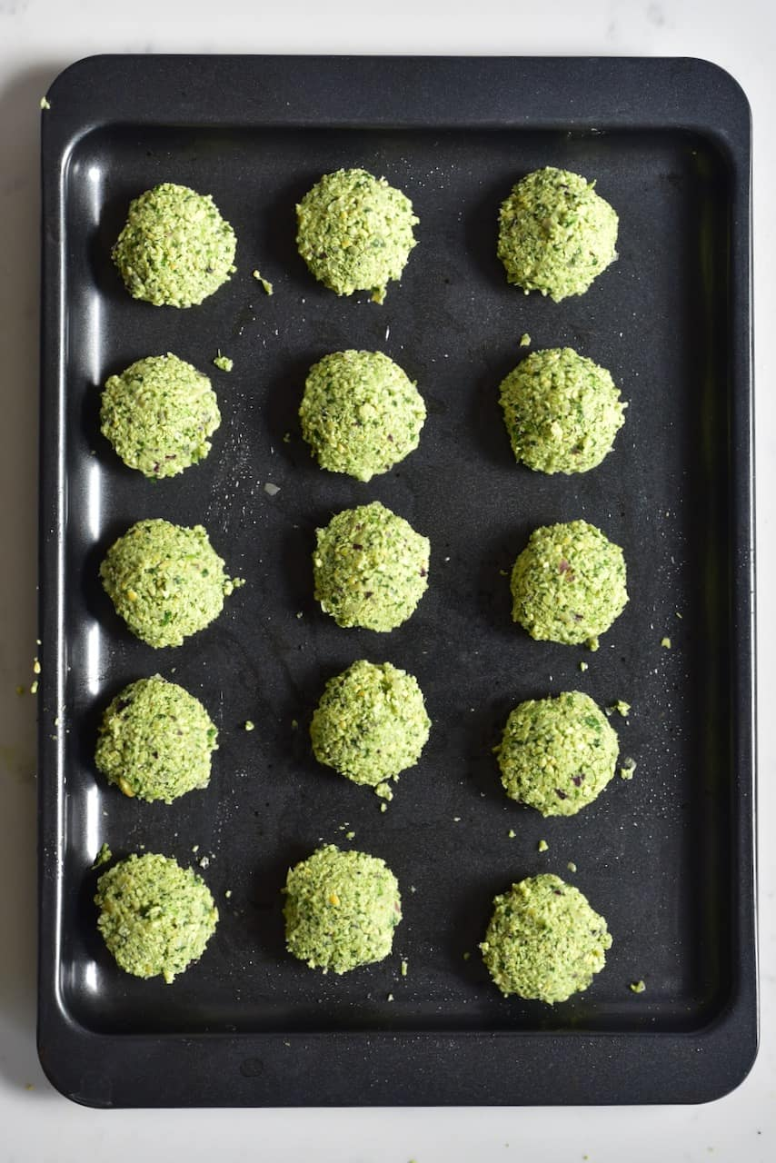 uncooked small falafel balls on top of a baking tray