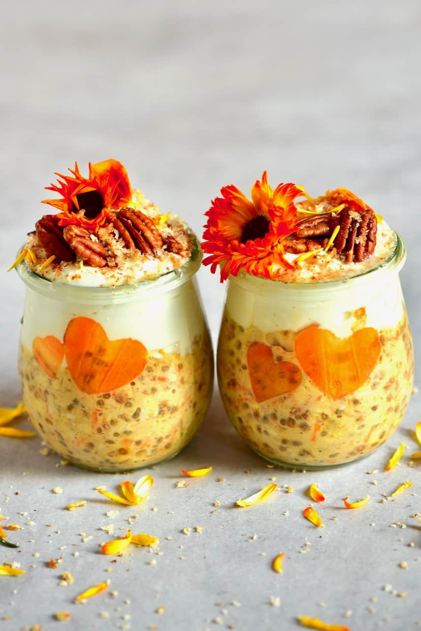 Two jars of carrot cake overnight oats decorated with pecans and edible flowers