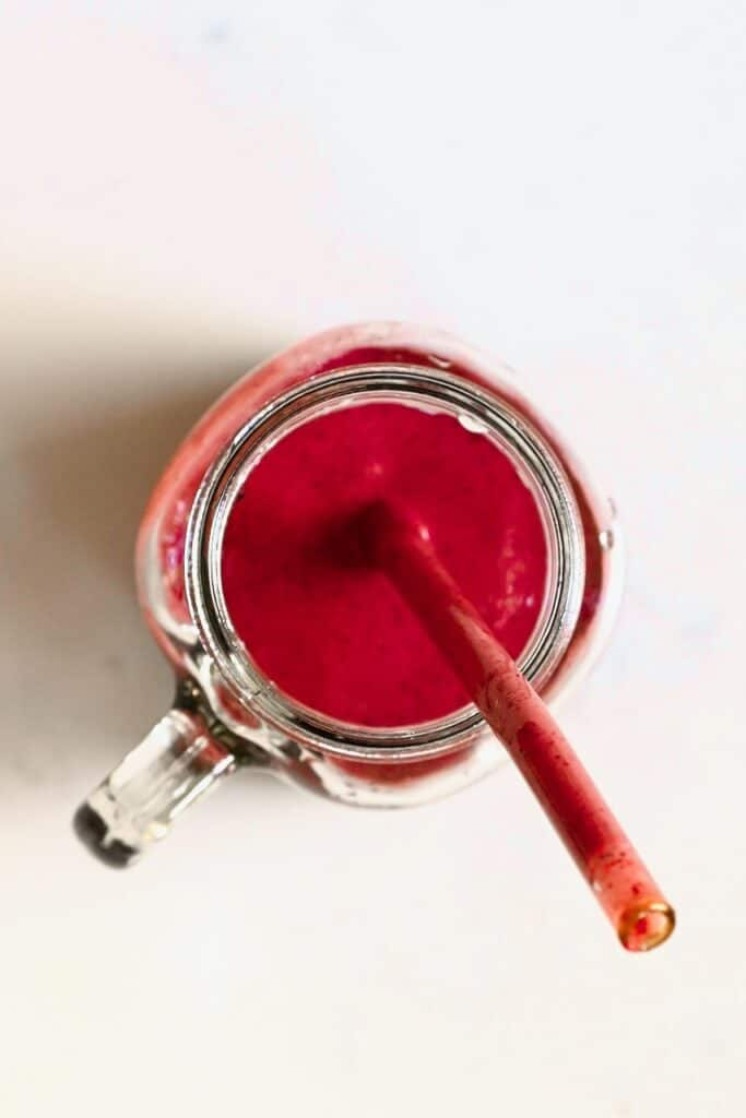 berry smoothie in a jar with a straw