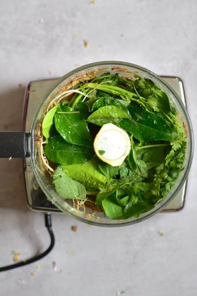 Adding coriander and kaffir leaves to a blender