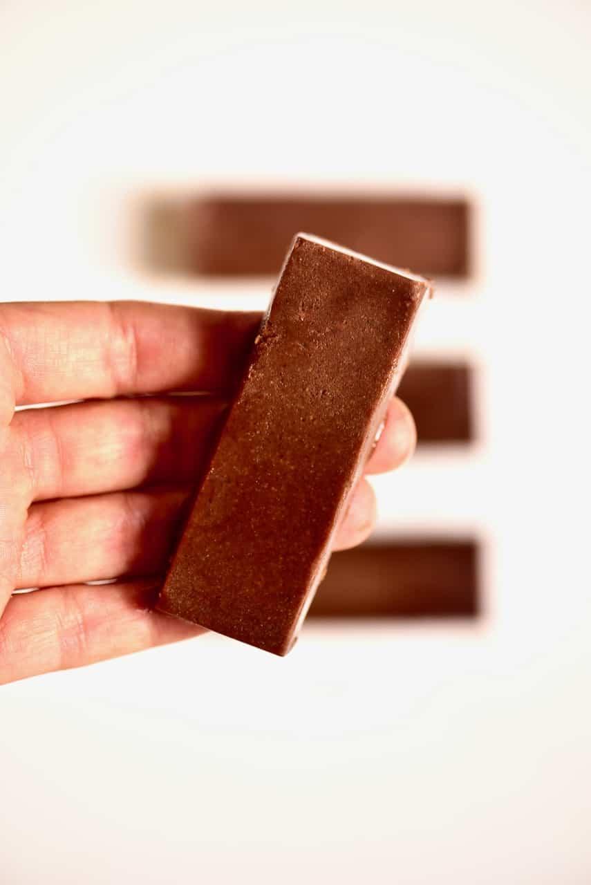 chocolate fudge bar on a hand- vegan fudge