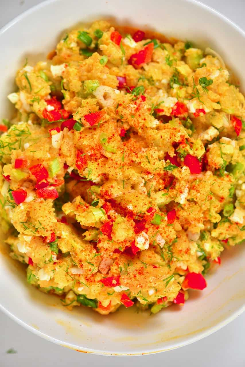 Bowl of egg potato salad with a sprinkle of chilli powder