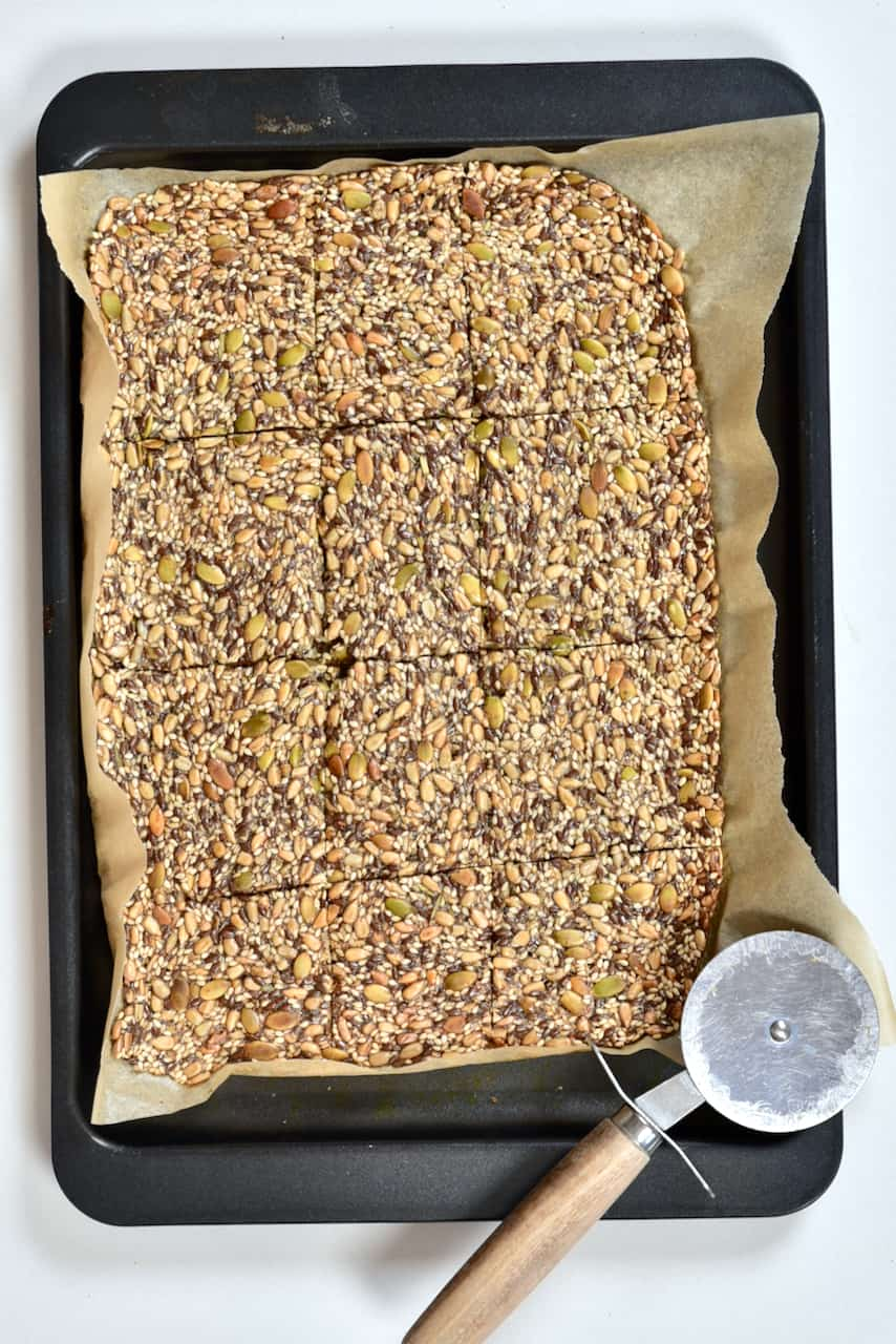 Cutting baked seeded crackers - keto crackers. healthy seed crackers in tray