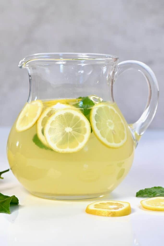 Fresh lemonade jug with lemon slices on the side