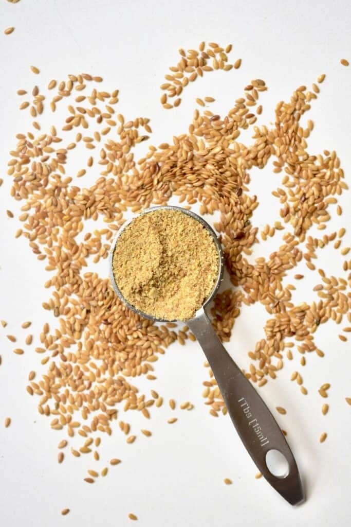 Tablespoon of ground Flaxseed next to unground flaxeed