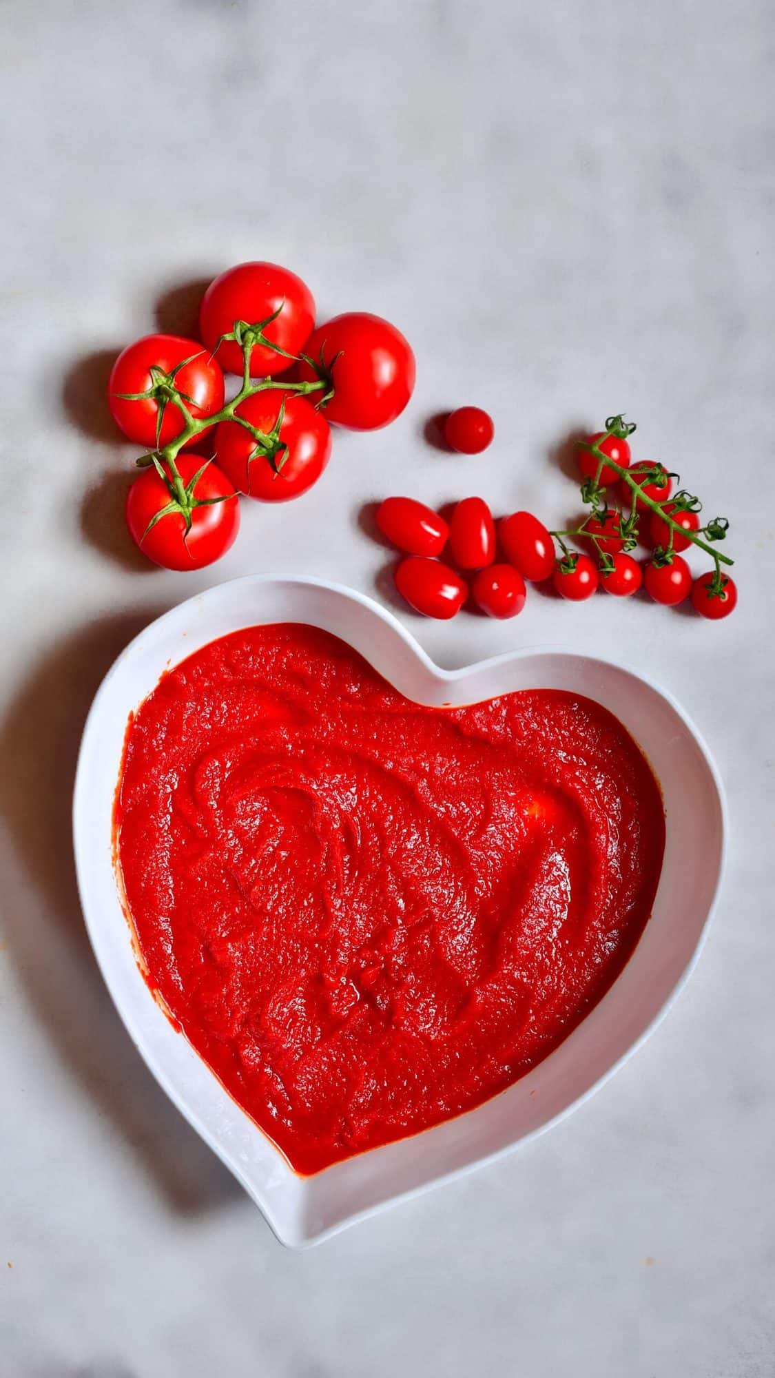 Tomato paste in a large bowl and tomatoes next to it