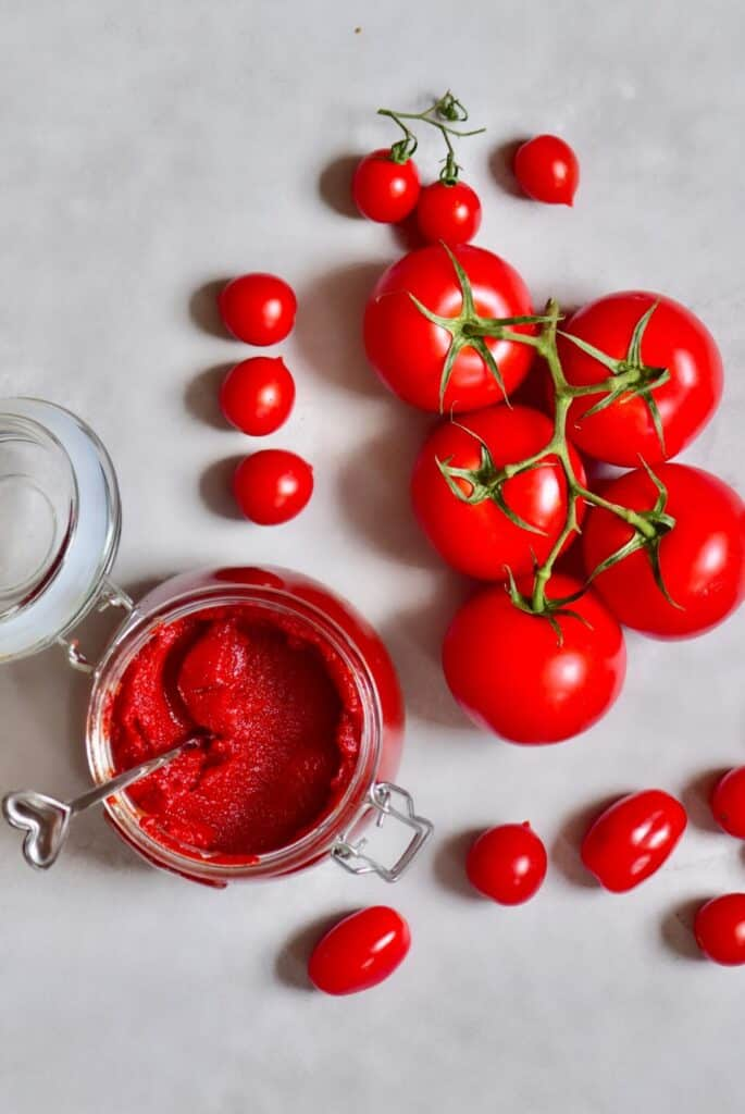 Tomato puree in a jar and tomatoes next to it