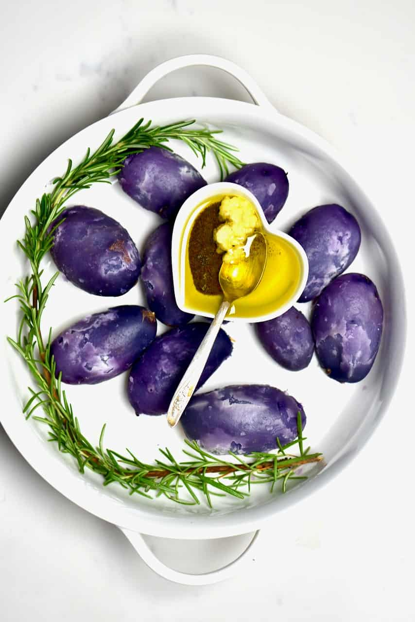 boiled purple potatoes and rosemary and dressing in white bowl