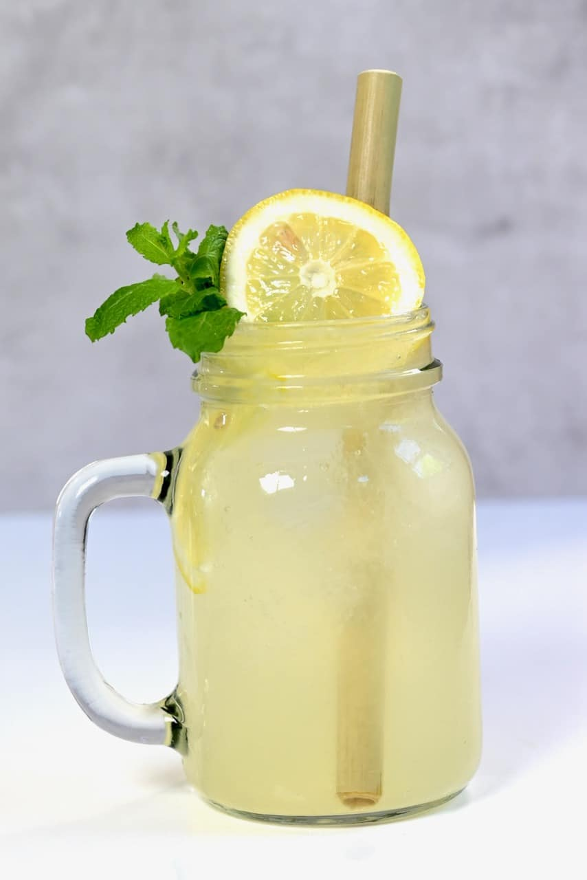 fresh lemonade in mason jar with lemon and mint and straw