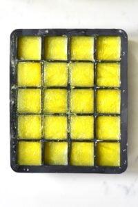 frozen ginger juice inside a black ice cube tray