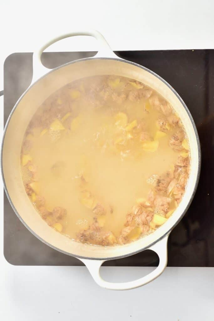 ginger and boiling water in a white pot
