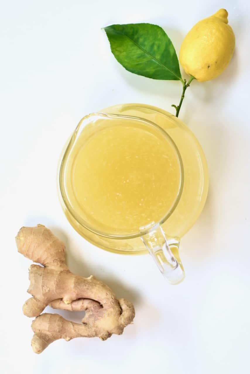ginger lemonade jug and ginger root and lemon on the side