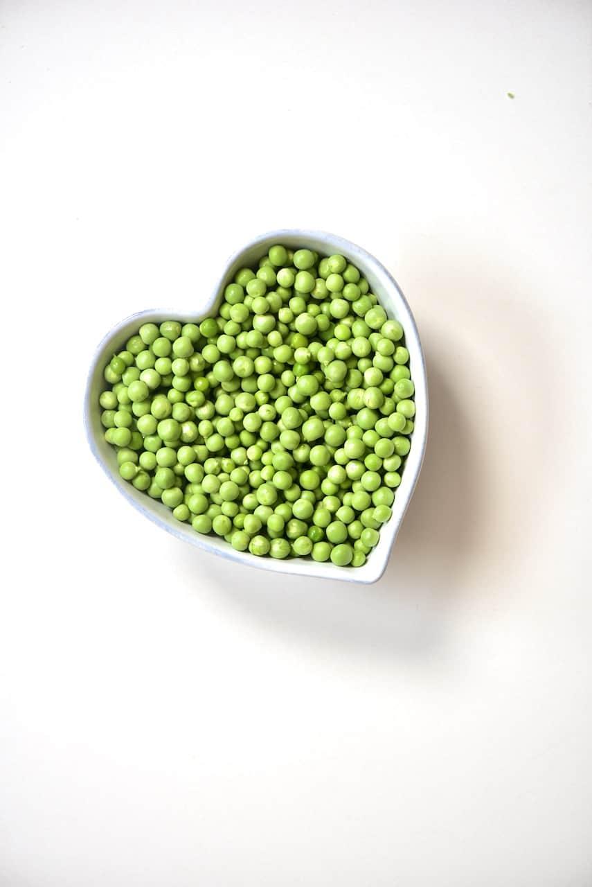 green peas inside a heart shaped bowl