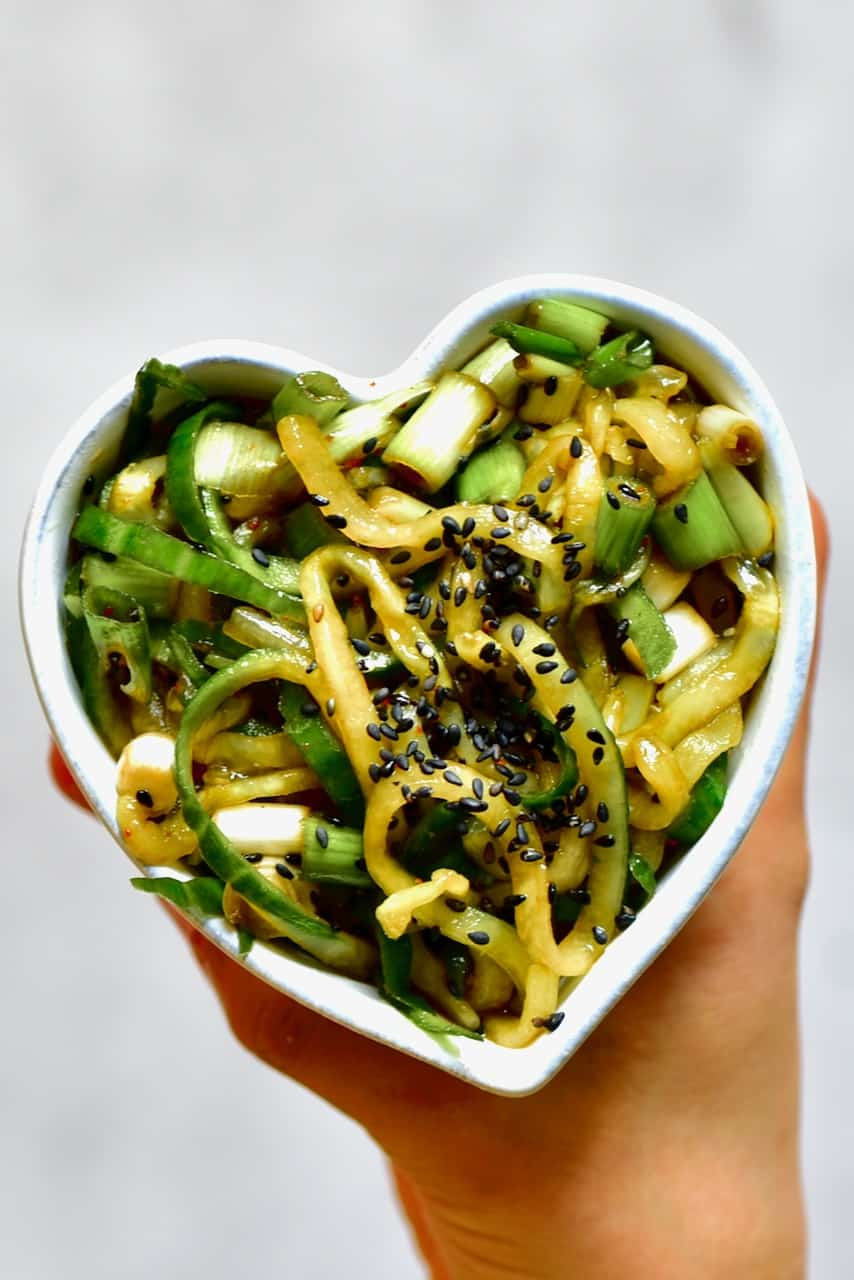 hand holding asian cucumber salad in a heart shaped bowl