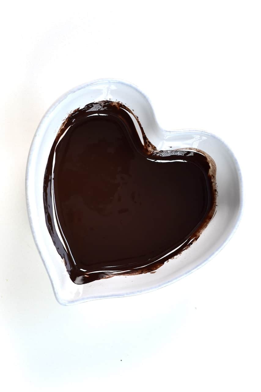 melted dark chocolate in a heart shaped bowl