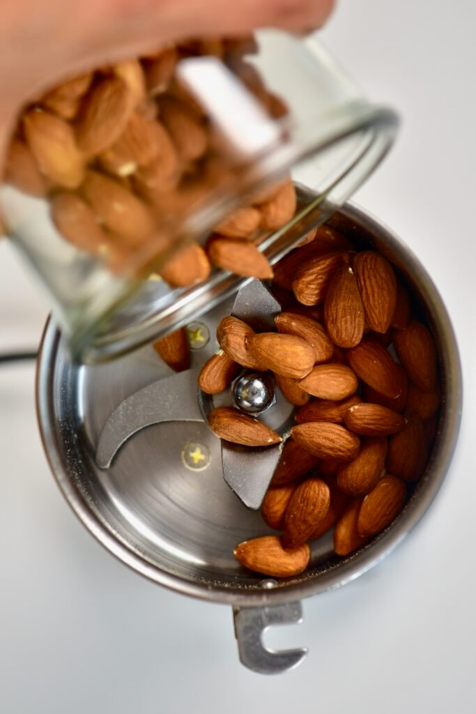 pouring almonds into grinder