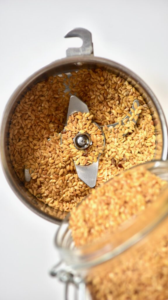 pouring golden Flaxseed into a spice grinder
