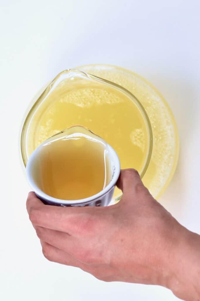 pouring honey on ginger lemonade