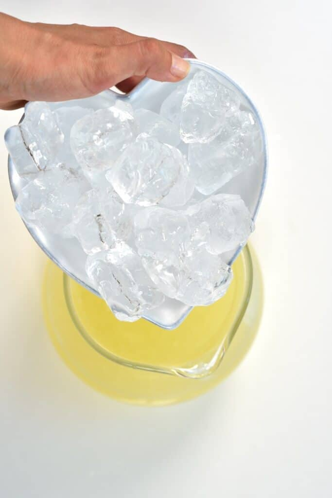 pouring ice cubes into lemonade jug