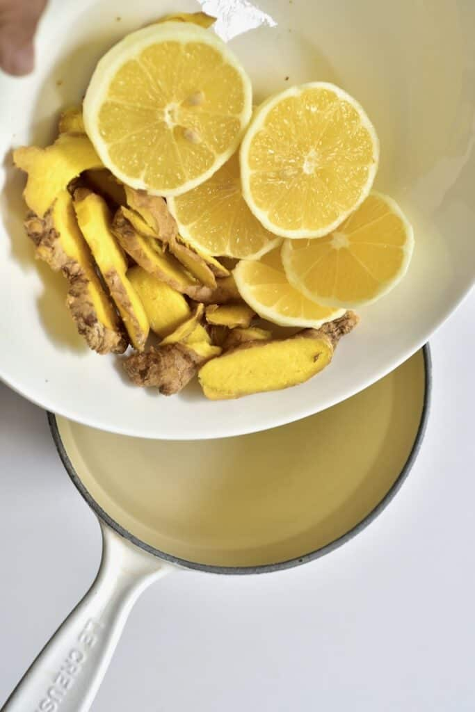 adding ginger and lemon slices to saucepan with water