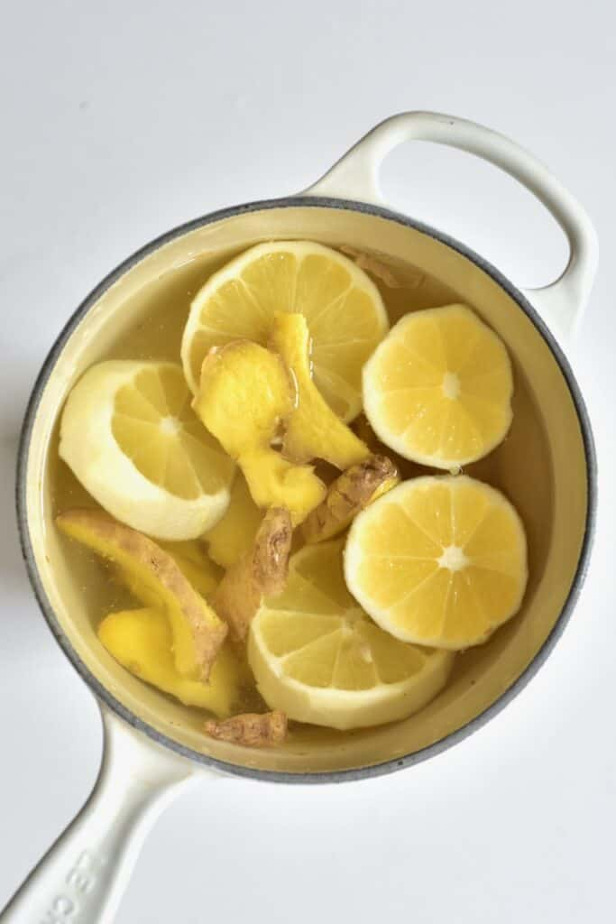 slices of lemon and ginger in water in a white pot
