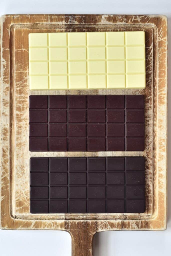 white milk and dark chocolate bars on cutting board
