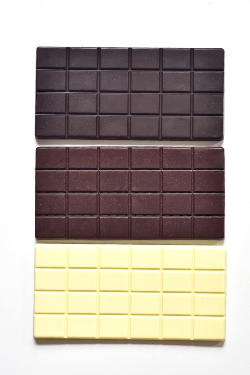 white milk and dark chocolate bars on white marble